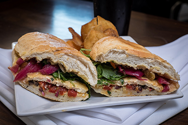 Joe's Deli - Johnny Be Good, Marinated crispy tofu, olive salad, hummus, roasted red peppers, pickled onions and arugula on grilled French bread. (Vegetarian)
