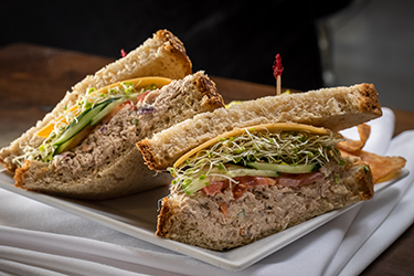 Joe's Deli - Gill's Tuna Monster, Homemade tuna salad with cucumber, tomato, and sprouts, topped with cheddar cheese on multi-grain.