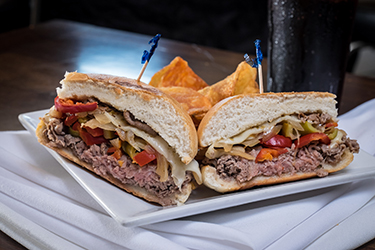 Joe's Deli - Italian Beef, Sliced roast beef with hot cherry peppers, sautéed onions, and melted provolone on a hard roll.